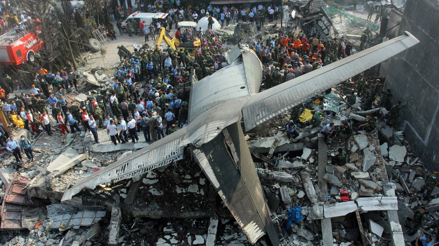 Rescuers search for victims at the site of an Indonesian air force cargo plane crash in Medan, Indonesia, on June 30.