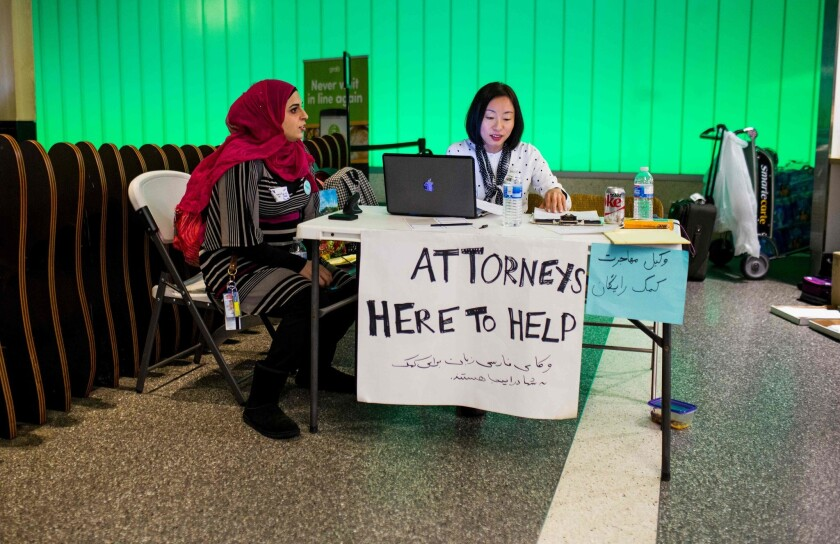 Volunteer translator Nour Our, left, and volunteer attorney Kat Choi sit in the arrivals at LAX during a protest of an executive order by President Trump.