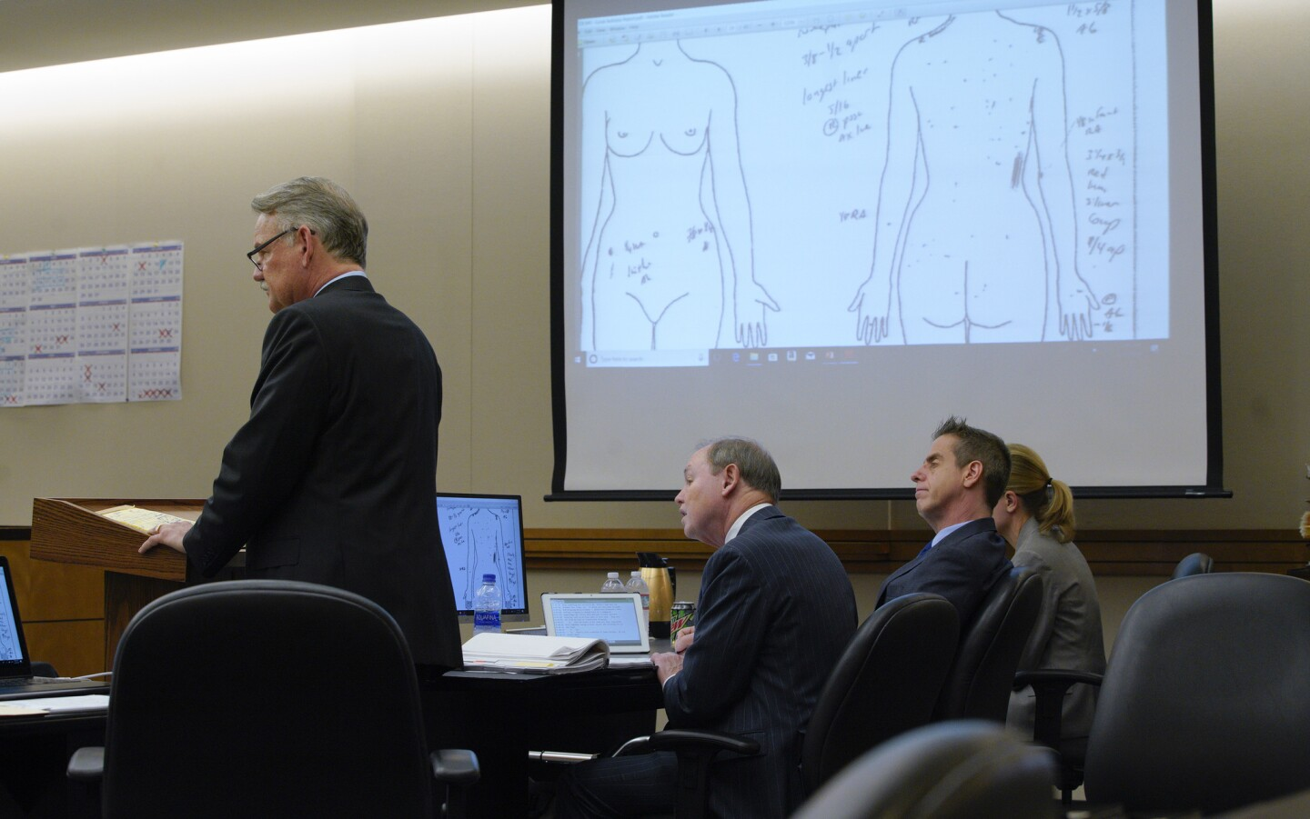Defendant Adam Shacknai sits at the defense table with his attorneys, Dan Webb and Krista M. Enns, as Dr. Cyril Wecht, forensic pathologist is questioned on the witness stand by plaintiff attorney, Keith Greer about the injuries to Rebecca Zahau s head.