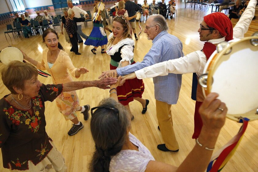 April 12, 2015. San Diego, CA. ..The Performing Folk Dancers of Balboa Park demonstrate various forms of Italian dancing during the International Folk Dance Spring Festival at the Balboa Park Club in Balboa Park. Here, dancer Ruth Clawson, left, introduces festival attendees to some dance steps... Nancee E. Lewis / Nancee Lewis Photography. No other reproduction allow with out consent of licensor. Permission for reproduction required..