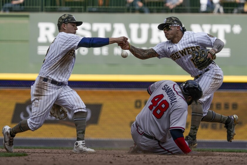 Milwaukee Brewers' Kolten Wong and Luis Urias fumble the ball as Atlanta Braves' Pablo Sandoval slides safely into second during the seventh inning of a baseball game Sunday, May 16, 2021, in Milwaukee. (AP Photo/Morry Gash)