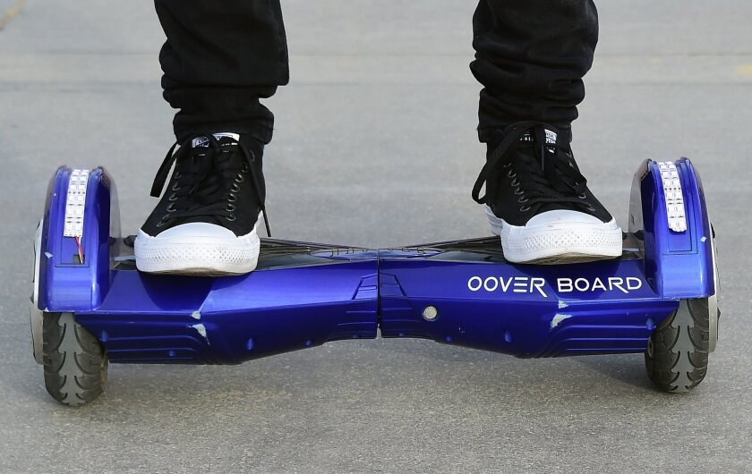 Michael Tran uses his hoverboard on the Venice Beach Boardwalk on December 10, 2015. Authorities say a hoverboard that was being charged caused a fire that damaged a Van Nuys home.