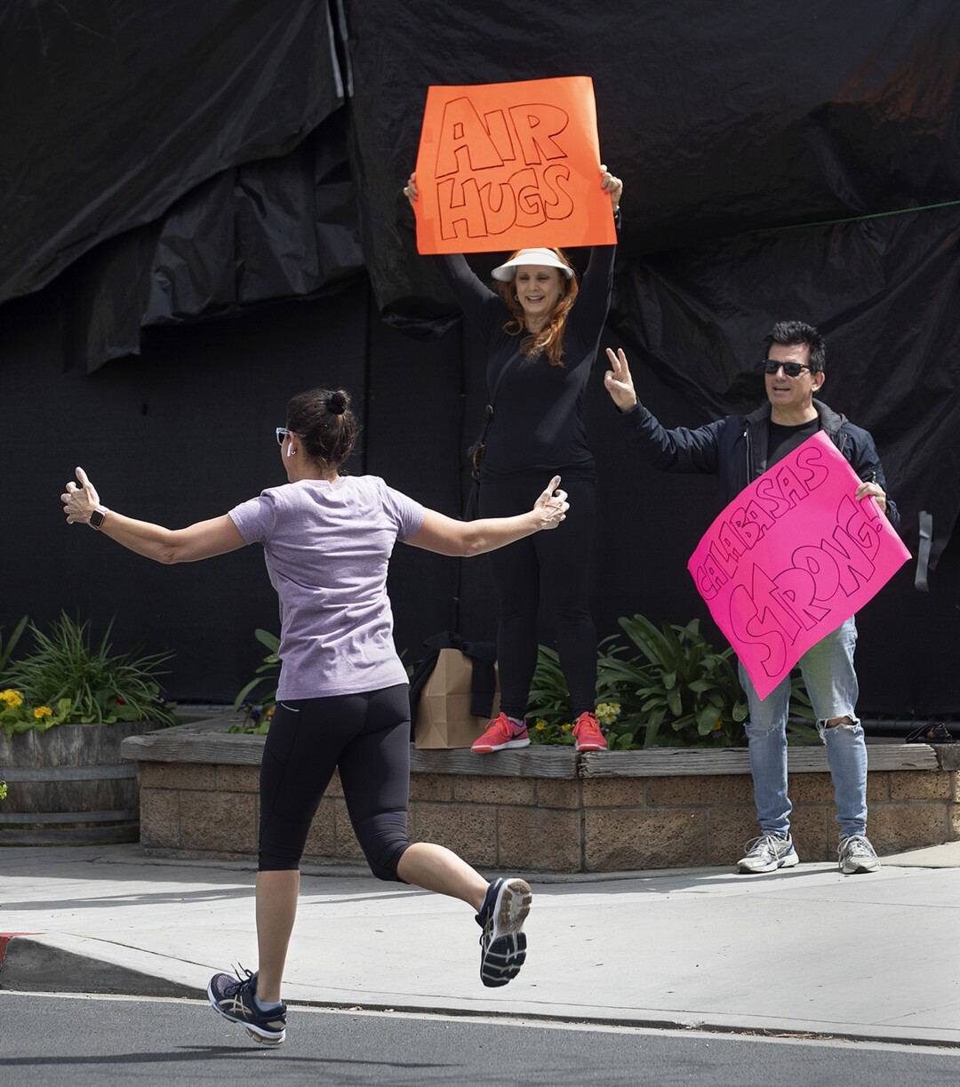 Juliann Hartman, center, and her husband, Butch, do their part to cheer people up during the pandemic by holding signs of encouragement on Calabasas Road in Calabasas.