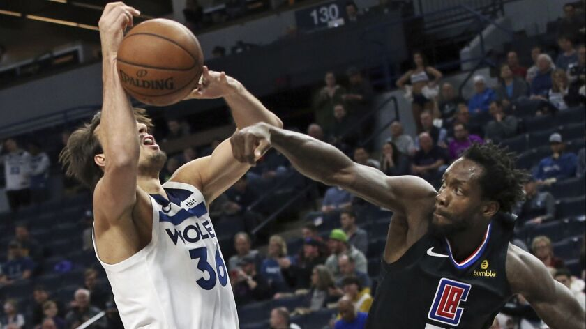 Clippers' Patrick Beverley, right, knocks the ball away from Minnesota Timberwolves' Dario Saric in the first half on Tuesday in Minneapolis.