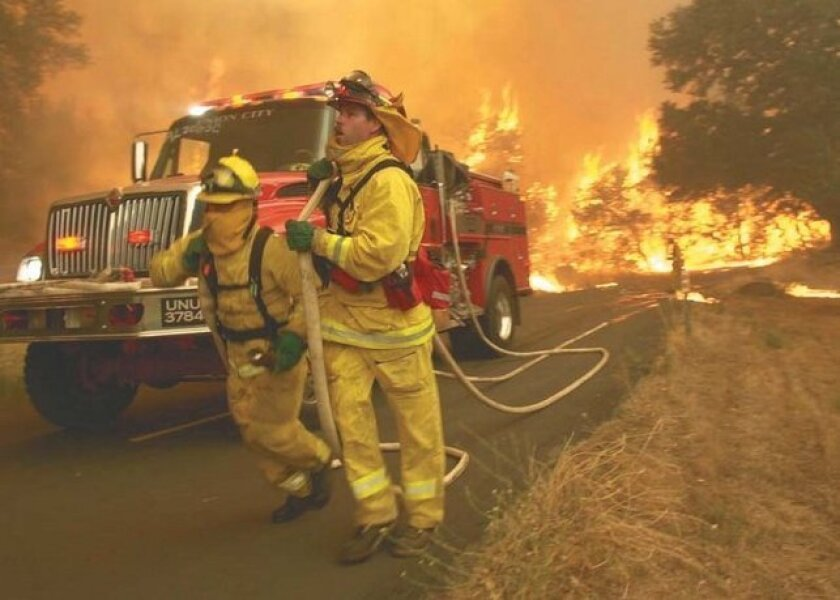 Firefighters run to put water on part of a backfire lit on Hoskings Ranch Road to deny fuel to the main part of the Cedar Fire in San Diego County in October 2003.