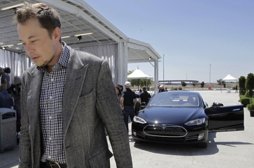 Elon Musk with a Tesla in the background