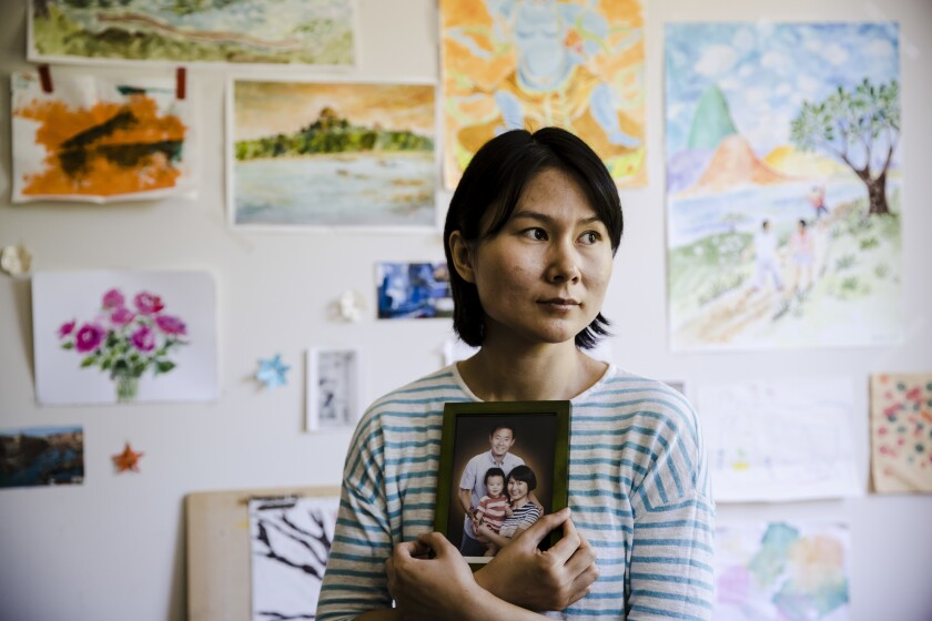 """FILE - In this Wednesday, May 9, 2018 file photo, Hua Qu, the wife of detained Chinese-American Xiyue Wang, poses for a photograph with a portrait of her family in Princeton, N.J. Iran's foreign minister says a detained Princeton graduate student will be exchanged for an Iranian scientist held by the U.S. Mohammed Javad Zarif made the announcement on Twitter on Saturday, Dec. 7, 2019. The trade involves graduate student Xiyue Wang and scientist Massoud Soleimani. Wang was sentenced to 10 years in prison in Iran for allegedly """"infiltrating"""" the country and sending confidential material abroad. His family and Princeton strongly denied the claims. (AP Photo/Matt Rourke, File)"""