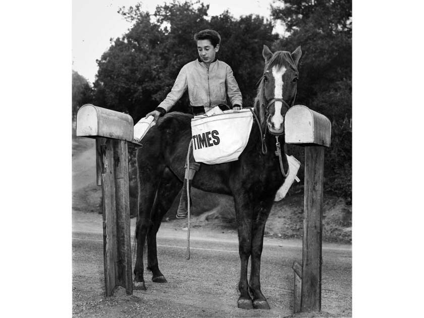 Oct. 1956: Los Angeles Times paperboy Jim Fitzgerald, 14, rides Quelty on his route through Sleepy H
