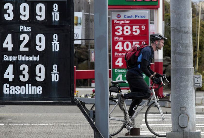 A bicyclist waits at an intersection between competing gas stations and multiple posted gas prices Monday in Seattle.