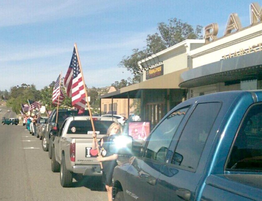 Ramona residents line Main Street in Old Town with U.S. flags provided by Ramona Rotary Club as Marine Sgt. Toran Gaal rides through on a hand-propelled recumbent bicycle on his cross-country trip.