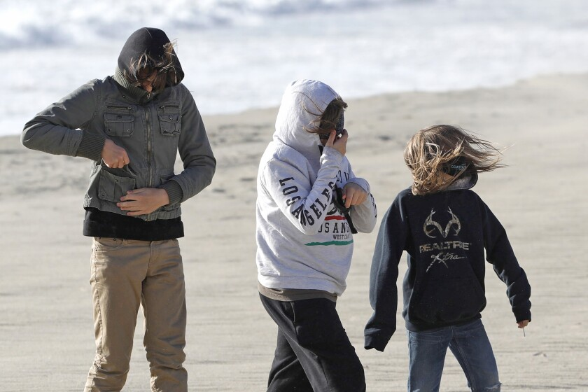 Three boys braves getting sand-blasted as they walk on Laguna's Main Beach on Monday.