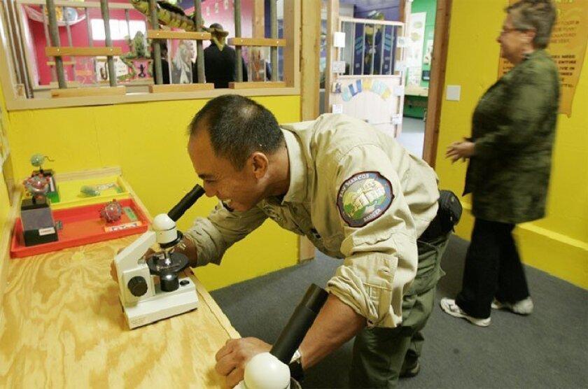 Ranger Ron Vinluan checked a bacteria slide in the Conservation  Barn during a tour yesterday. (Eduardo Contreras / Union-Tribune)