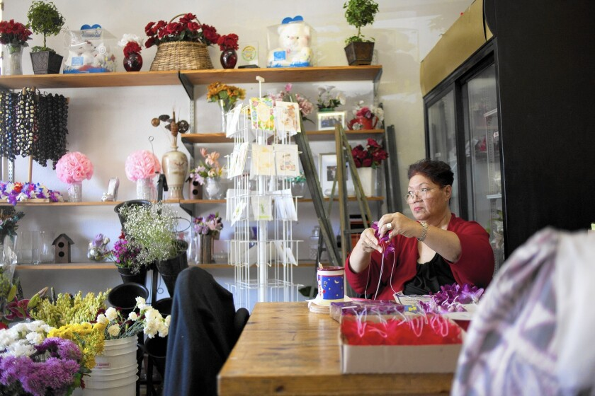 Nellie Lua adds flowers to a lei at Island Lei and Bouquet in Carson.