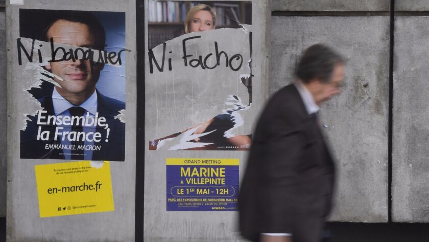 A man walks by graffiti-marred election campaign posters in Rennes on Tuesday. The graffiti reads ""