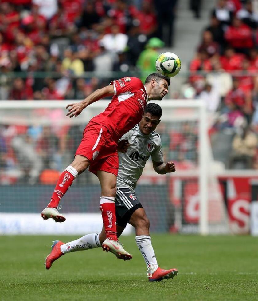 El jugador de Toluca Emmanuel Gigliotti (i), pelea por el balón con Anderson Santamaría de Atlas este domingo, durante el juego correspondiente a la jornada 11 del torneo mexicano de fútbol, celebrado en el estadio Nemesio Diez, en la ciudad de Toluca (México). EFE