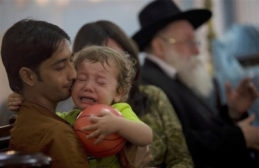 Moshe Holtzberg, the 2-year-old orphan of the rabbi and his wife slain in the Mumbai Jewish center, cries during a memorial service at a synagogue in Mumbai, India, Monday, Dec. 1, 2008. Holtzberg will fly to Israel Monday on an Israeli Air Force jet with his parents' remains and the Indian woman who rescued him, an Israeli Foreign Ministry spokesman said. (AP Photo)