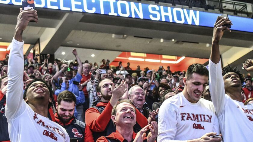 Mississippi coach Kermit Davis and players watch the broadcast of the NCAA Division I men's basketball tournament selection show in Oxford, Miss., on Sunday.
