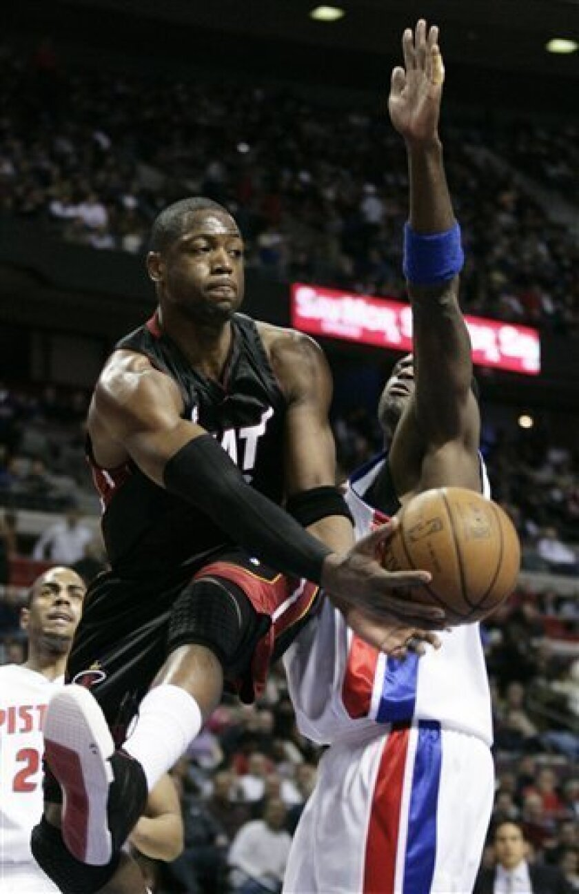 Miami Heat guard Dwyane Wade passes off against Detroit Pistons forward Antonio McDyess, right, during the first half of an NBA basketball game Wednesday, Feb. 4, 2009, in Auburn Hills, Mich. (AP Photo/Duane Burleson)