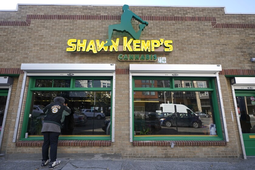 """Kris """"Sonics Guy"""" Brannon, a Seattle SuperSonics superfan, looks in the window of Shawn Kemp's Cannabis, the marijuana dispensary owned by Shawn Kemp, a former NBA basketball player for the SuperSonics and several other teams, along with with several business partners, before the store's grand opening, Friday, Oct. 30, 2020, in downtown Seattle. (AP Photo/Ted S. Warren)"""