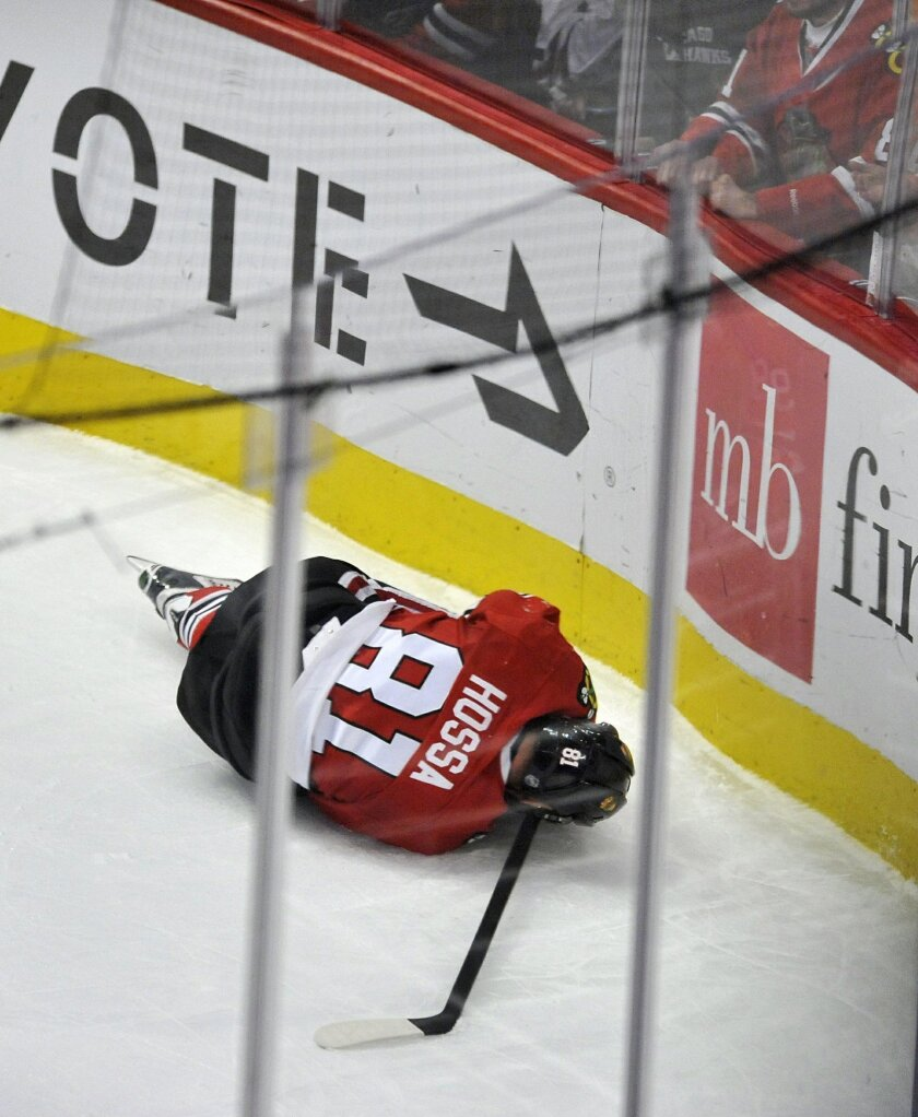 Chicago Blackhawks' Marian Hossa (81), of Slovakia, lies on the ice during the second period of an NHL hockey game against the Anaheim Ducks on Saturday, Feb. 13, 2016, in Chicago. Hossa left the game with a left leg injury. Anaheim won 3-2 in overtime. (AP Photo/Paul Beaty)