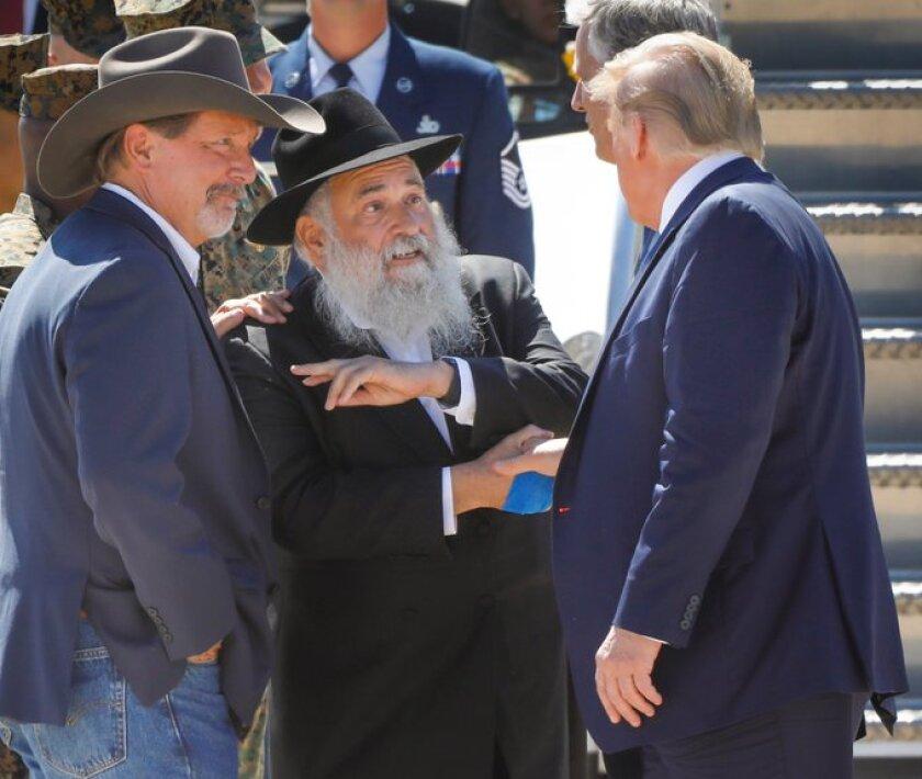 President Donald Trump is greeted by Poway Mayor Steve Vaus, (l) & Rabbi Yisroel Goldstein,