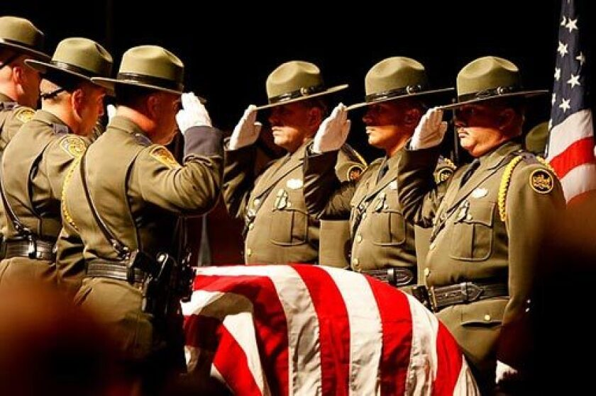 The Border Patrol honor guard stands at attention before carrying agent Robert Rosas' flag-draped coffin from a memorial service at the Southwest High School theater in El Centro.