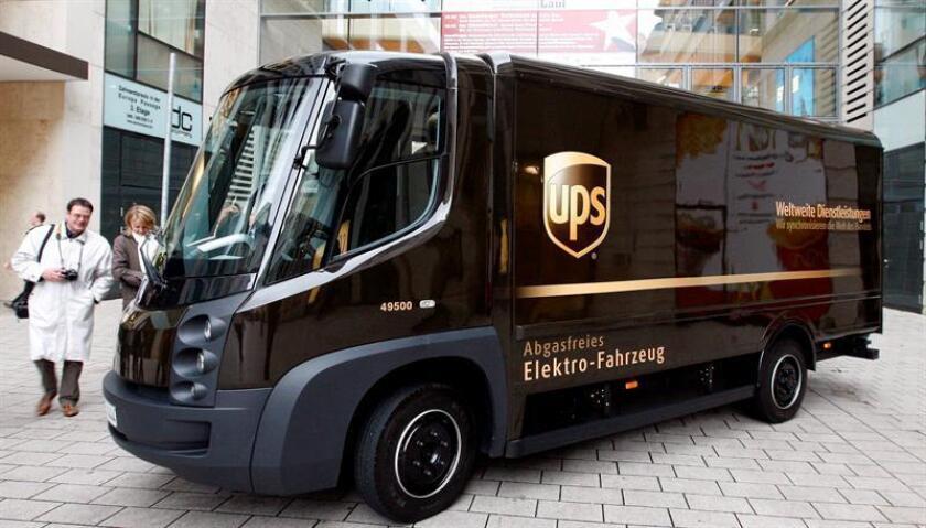Personas pasan delante del primer coche eléctrico de la compañía UPS, en Hamburgo, Alemania, hoy 20 de noviembre de 2008. La compañía estadounidense de paquetería y mensajería United Parcel Services (UPS) planea entregar parte de su envios de Hamburgo en este nuevo vehículo que puede recorrer 80 km con total autonomía a una velocidad de entre 90 y 100 kms. EFE/Archivo