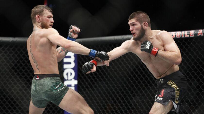 Conor McGregor, left, fights Khabib Nurmagomedov during a UFC 229 mixed martial arts bout Saturday,