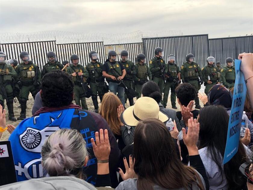 Un grupo de manifestantes, en su mayoría religiosos, se confronta a miembros del Servicio de Protección Federal (FPS) durante un acto de desobediencia civil en apoyo a la caravana migrante, cerca del muro fronterizo entre Tijuana (México) y San Diego (California, EE.UU.). EFE/Archivo