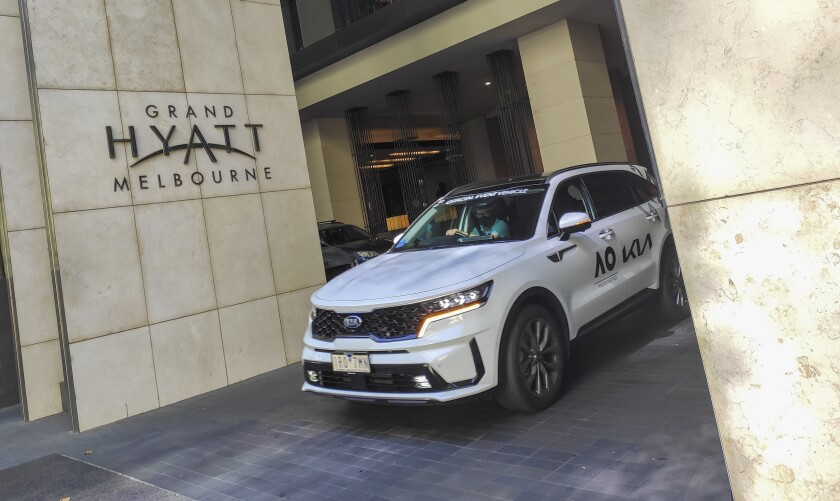 An Australian Open courtesy car waits outside the Grand Hyatt hotel in central Melbourne, Australia, Thursday, Feb. 4, 2021. All competition at six Australian Open tuneup events scheduled for Thursday was called off after a worker at one of the tournaments' Melbourne quarantine hotels tested positive for COVID-19. (AP Photo/Hamish Blair)