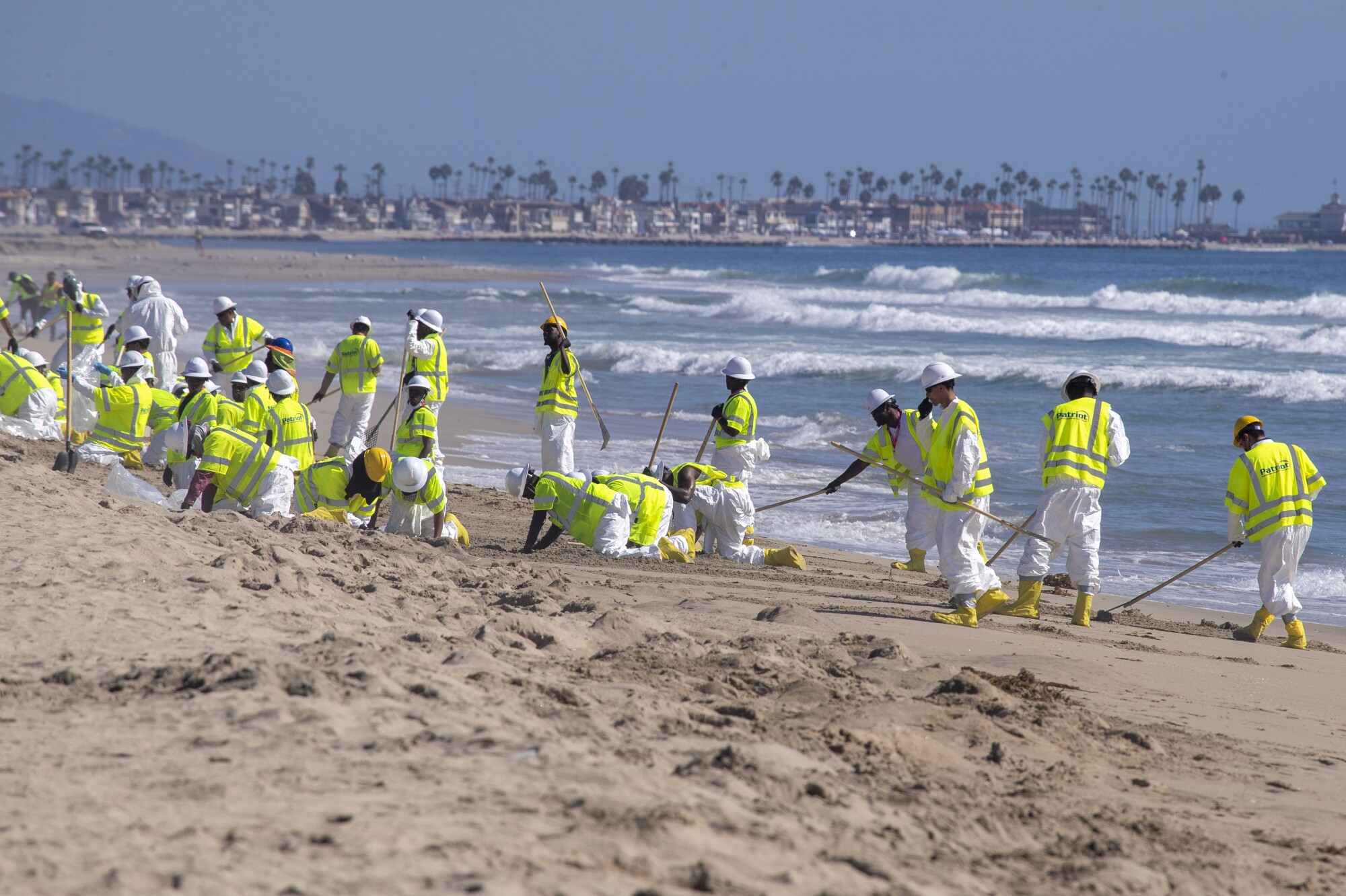 Oil spill cleanup crew members from New Jersey clean up the oil spill at Huntington State Beach on Oct. 10.