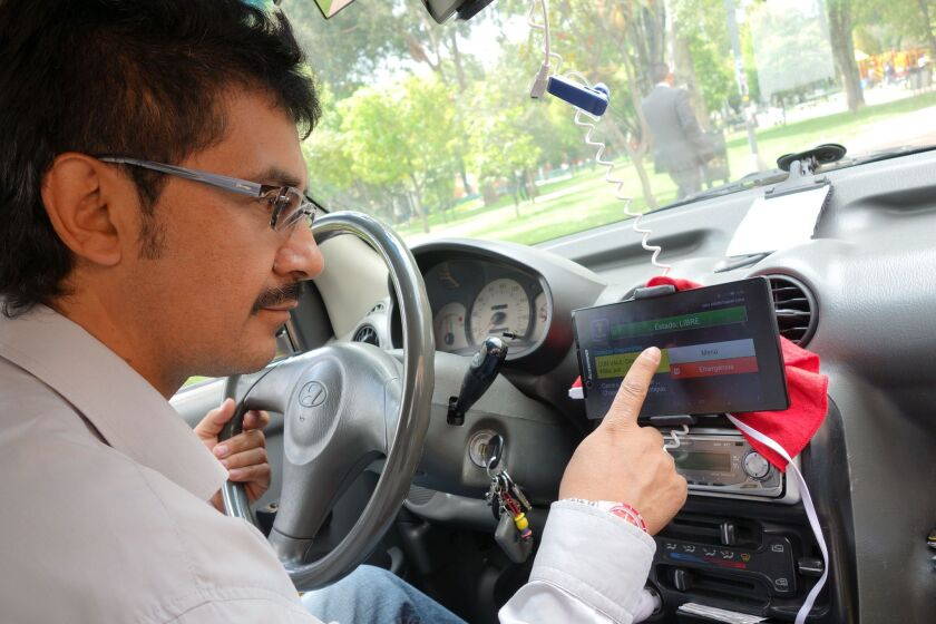 Bogota driver Jairo Duarte checks a fare opportunity coming over his Tappsi Internet-GPS service, one of several ride-share apps available in the Colombian capital.