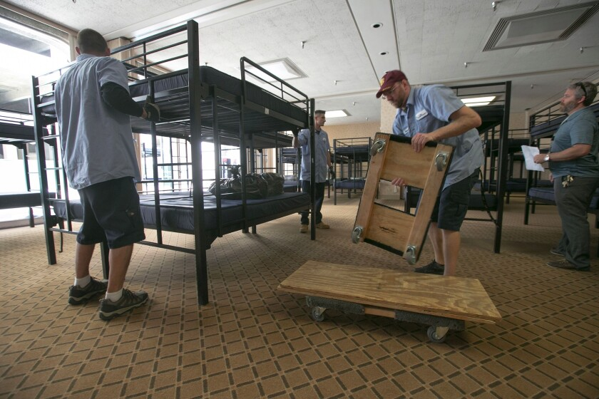 In this photo from April, workers are seen setting up beds in Golden Hall for what at the time was believed to be a temporary shelter. On Tuesday, the City Council voted to expand the shelter by 138 beds.