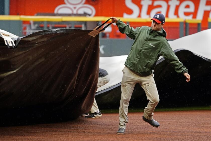 Un empleado de mantenimiento del estadio de los Bravos de Atlanta cubre con una lona el terreno previo a un partido contra los Rockies de Colorado, el jueves 16 de septiembre de 2021, en Atlanta. (AP Foto/John Bazemore)