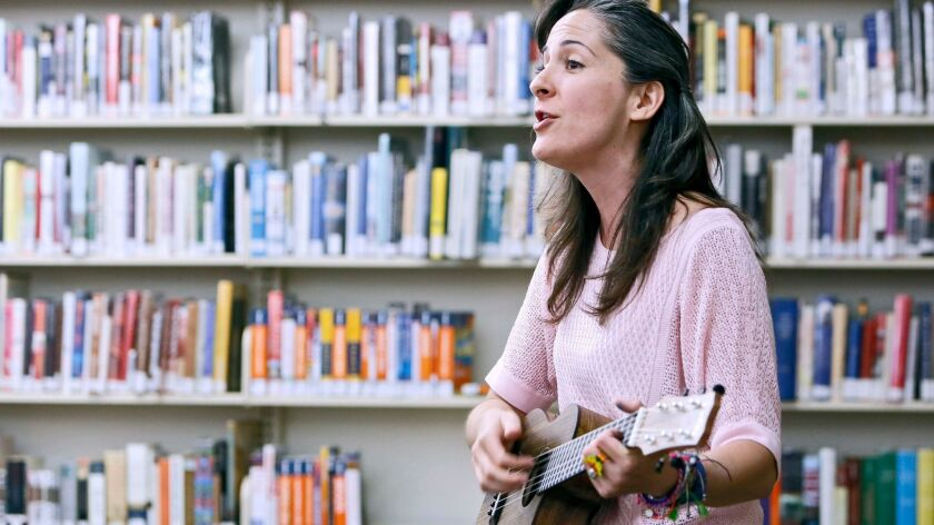 Music teacher Sara Quintanar plays some of her English-Spanish songs for children at the Pacific Par