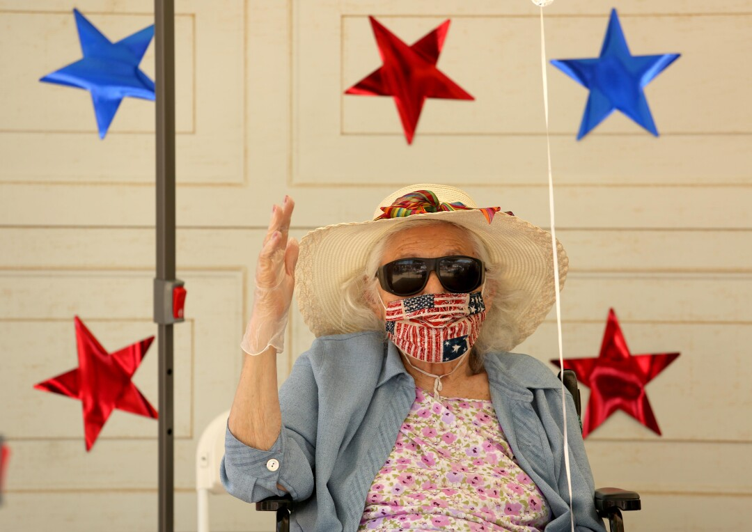 A resident of Mom & Dad's House waves while members of the public drive by to celebrate World War II veteran Lt. Col. Sam Sachs' 105th birthday.
