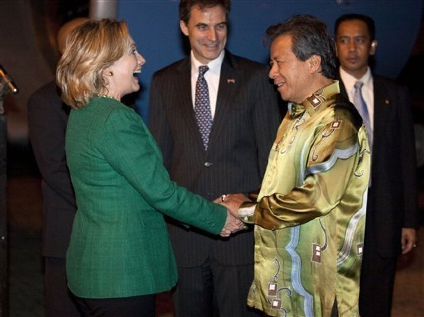 U.S. Secretary of State Hillary Rodham Clinton, left, smiles after being received by Malaysian Foreign Minister Anifah Aman at SkyPark Subang Terminal on Monday, Nov. 1, 2010 in Subang, Malaysia. (AP Photo/Evan Vucci, Pool)