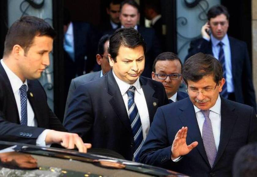 Turkish Foreign Minister Ahmet Davutoglu, right, leaves a meeting on Syria with army generals and other officials in Ankara, Turkey's capital.