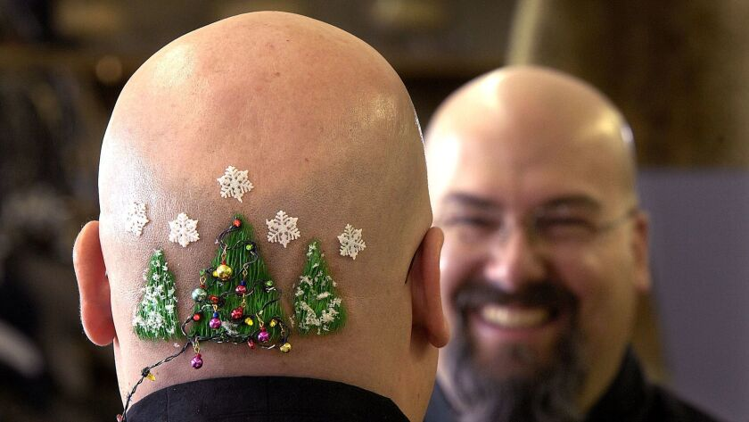 Steve Schaak shows the Christmas trees, complete with tiny lights, decorating his head Saturday, Dec