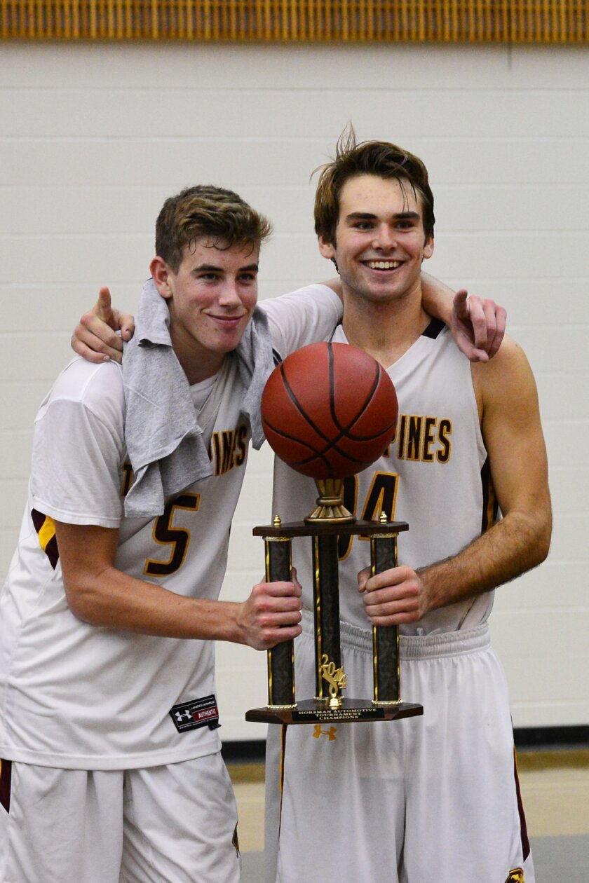 Torrey Pines Falcons seniors Marek Sullivan and Connor Milmoe celebrate their Horsman Automotive-Wolf Pack Tournament win on Dec. 15. Milmoe was named the tournament MVP. Photo by Anna Scipione