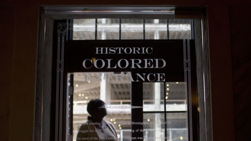 In this Jan. 7, 2016 photo, a woman stands in the doorway of then new Historic Colored Entrance at the Lyric Theatre, in Birmingham, Ala.