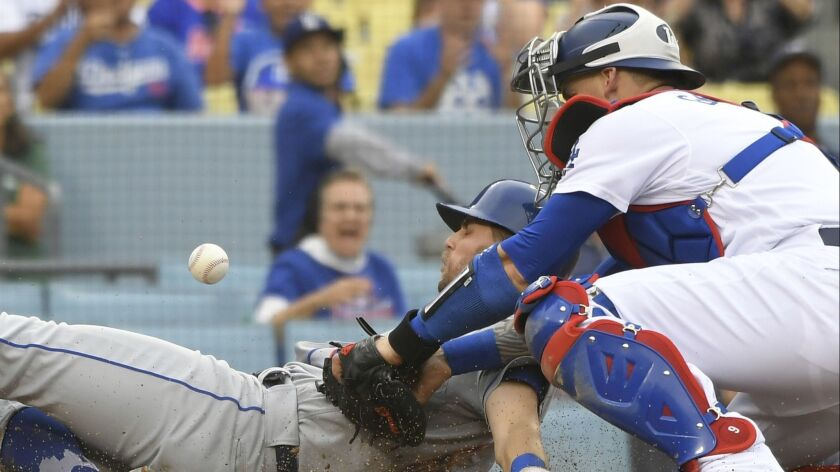 New York Mets second baseman Jeff McNeil is safe at home as Los Angeles Dodgers' Yasmani Grandal los