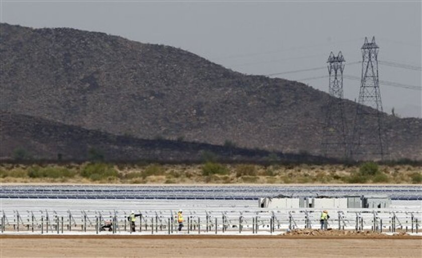 Workers continue to build rows of solar panels at a Mesquite Solar 1 facility under construction Friday, Sept. 30, 2011, in Arlington, Ariz. The new solar facility is part of a $1 billion Energy Department loan guarantee, of which $337 million is going to Mesquite Solar 1, for the 150 megawatt solar facility. (AP Photo/Ross D. Franklin)