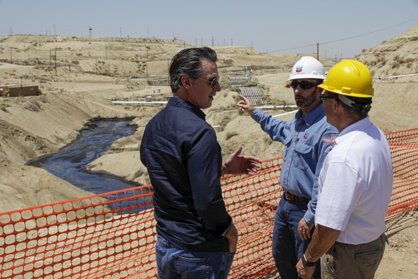 Gov. Gavin Newsom is briefed on a million-gallon spill in McKittrick by Billy Lacobie of Chevron, center, and Jason Marshall of California Department of Conservation Division of Oil, Gas and Geothermal Resources.