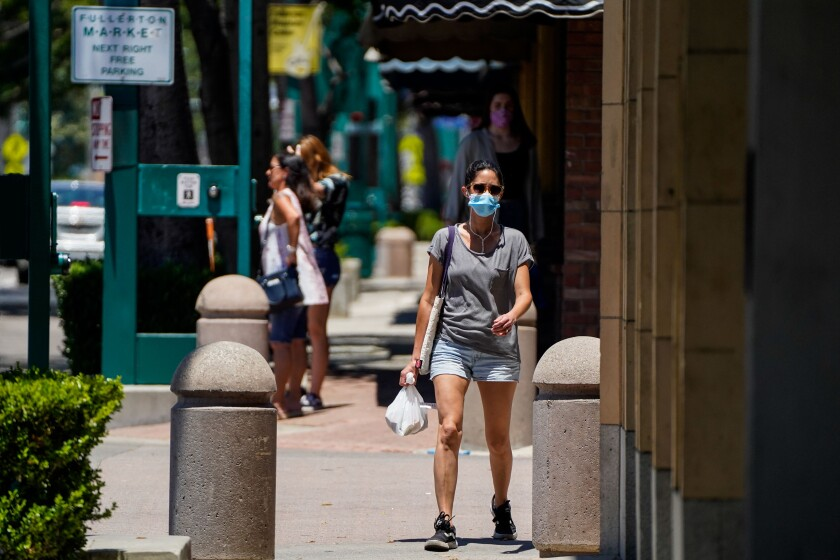 A masked woman walks along Harbor boulevard in downtown Fullerton on June 11.