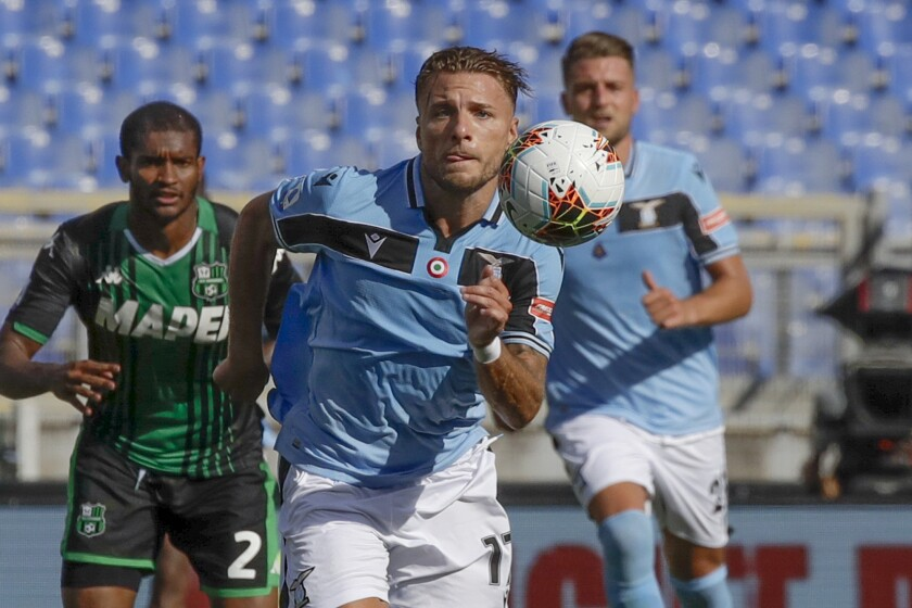 "FILE - In this Saturday, July 11, 2020 file photo, Lazio's Ciro Immobile eyes the ball during the Serie A soccer match between Lazio and Sassuolo at the Rome Olympic Stadium. Prolific scorer Ciro Immobile has extended his contract with Lazio through 2025. His previous contract was due to expire in 2023.""This is important, because Immobile had gained the attention of some big clubs, considering that he's the European Golden Shoe holder,"" Lazio communications director Stefano De Martino said Monday. (AP Photo/Alessandra Tarantino, File)"