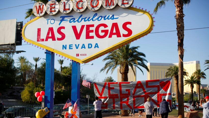 """People sign a banner next to the """"Welcome to Fabulous Las Vegas"""" sign at memorial to Route 91 music"""