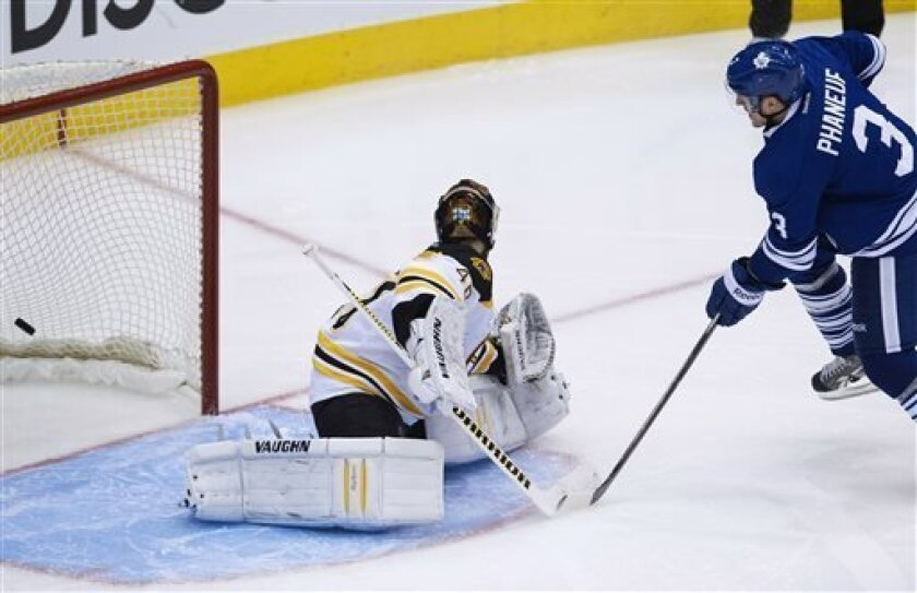 Toronto Maple Leafs defenseman Dion Phaneuf, right, scores past Boston Bruins goalie Tuuka Rask, left, during third period NHL hockey playoff action in Toronto on Sunday, May 12, 2013. (AP Photo/The Canadian Press, Nathan Denette)