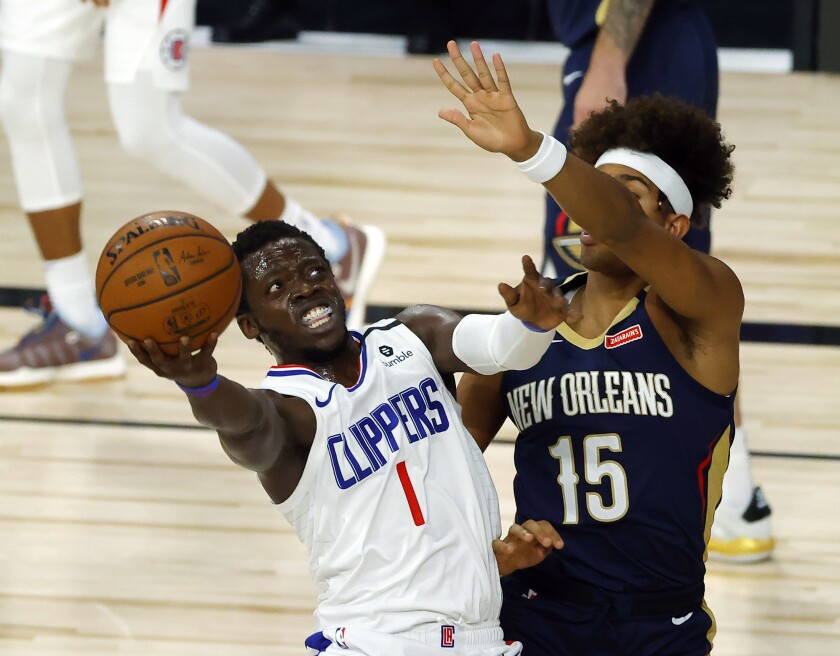 Los Angeles Clippers' Reggie Jackson (1) shoots against New Orleans Pelicans' Frank Jackson (15) during an NBA basketball game Saturday, Aug. 1, 2020, in Lake Buena Vista, Fla. (Kevin C. Cox/Pool Photo via AP)