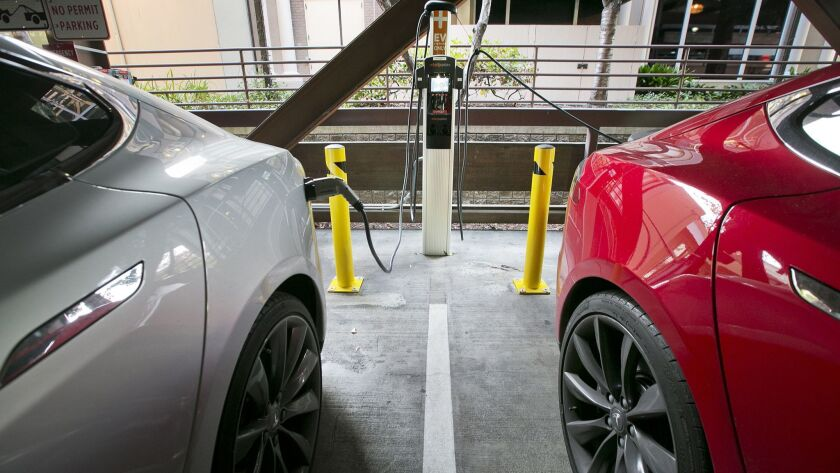 Two Teslas charge in a public garage in Palo Alto.